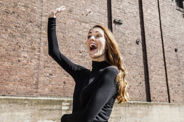Portrait of excited woman calling someone - FMKF05125