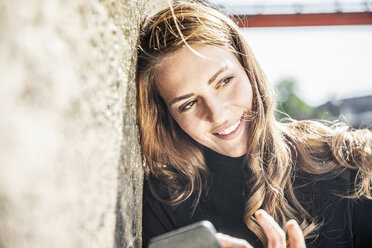 Portrait of smiling woman with smartphone leaning against wall - FMKF05128