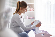 Pregnant woman with baby clothes in baby room - ABIF00527
