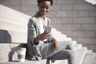 Portrait of smiling businesswoman sitting on stairs using earphones and smartphone - ABIF00542