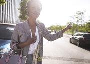 Portrait of businesswoman hailing a taxi - ABIF00545