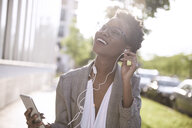 Portrait of happy businesswoman using smartphone and earphones - ABIF00548