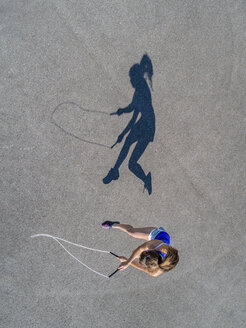 Aerial view of young woman skipping rope, shadow - STSF01597