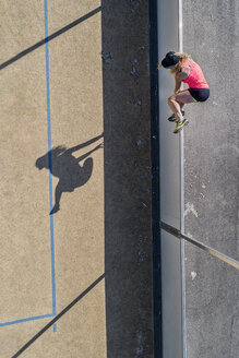 Aerial view of sportive woman jumping over barrier - STSF01603