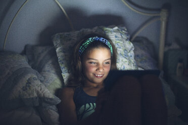 Girls in bed using digital tablet smiling - ISF09100