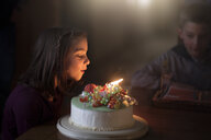 Girl blowing out candles on birthday cake - ISF09148