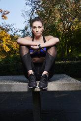 Sportive woman sitting on table tennis table - MMIF00115