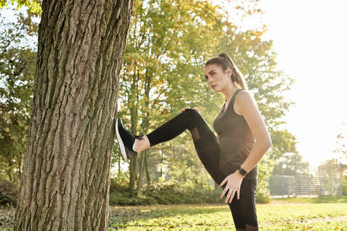 Sportive woman stretching leg on tree trunk - MMIF00127