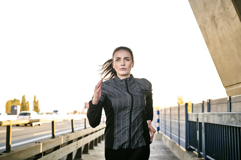 Portrait of sportive woman jogging - MMIF00130