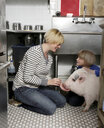 Mother and daughter sitting in kitchen stroking pet pig - ISF09165