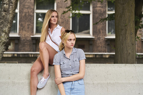 Two young women in the city looking sideways - MMIF00133