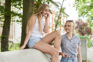 Two young women sharing cell phone and earphones outdoors - MMIF00136