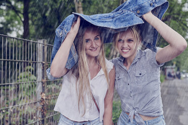 Two young women shletering from rain with a denim jacket - MMIF00139