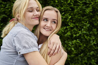 Two happy young women hugging a hedge - MMIF00142