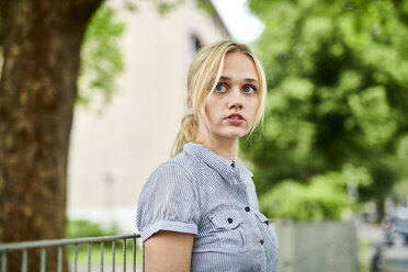 Serious blond young woman at a fence - MMIF00151