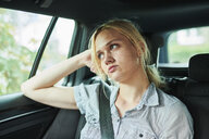 Serious blond young woman in a car - MMIF00154