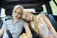 Two young woman sitting on backseat in a car - MMIF00157