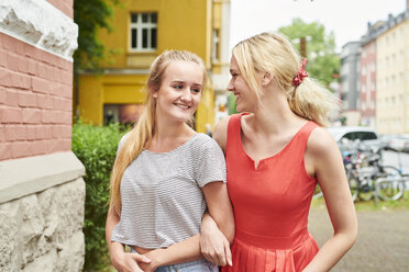 Two happy young women arm in arm in the city - MMIF00163