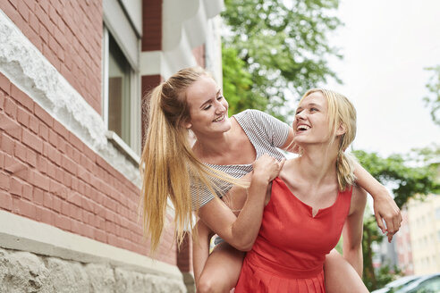 Happy young woman giving friend piggyback ride in the city - MMIF00169