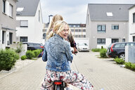 Two happy young women riding bicycle together on one bike - MMIF00172