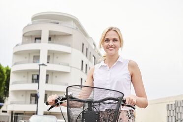 Portrait of smiling young woman with bicycle - MMIF00175