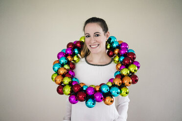 Portrait of smiling woman with colourful Christmas bauble wreath - MOEF01331