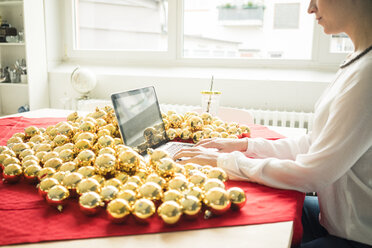 Woman sitting at table with many golden Christmas baubles working on laptop - MOEF01334