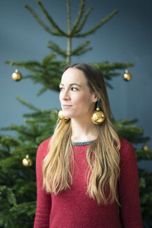 Portrait of woman wearing golden Christmas baubles earrings - MOEF01340