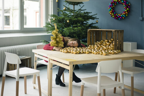 Woman sitting at table with many golden Christmas baubles - MOEF01343