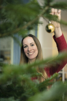 Portrait of smiling woman decorating Christmas tree - MOEF01346