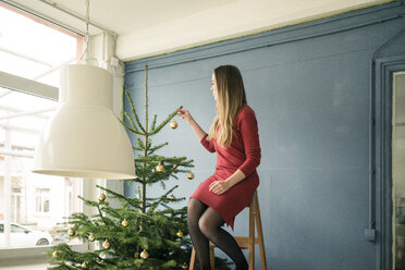 Woman sitting on ladder in a loft decorating Christmas tree - MOEF01349
