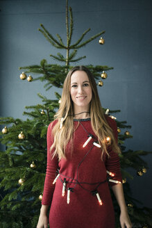 Portrait of smiling woman with chain of lights standing in front of Christmas tree - MOEF01352