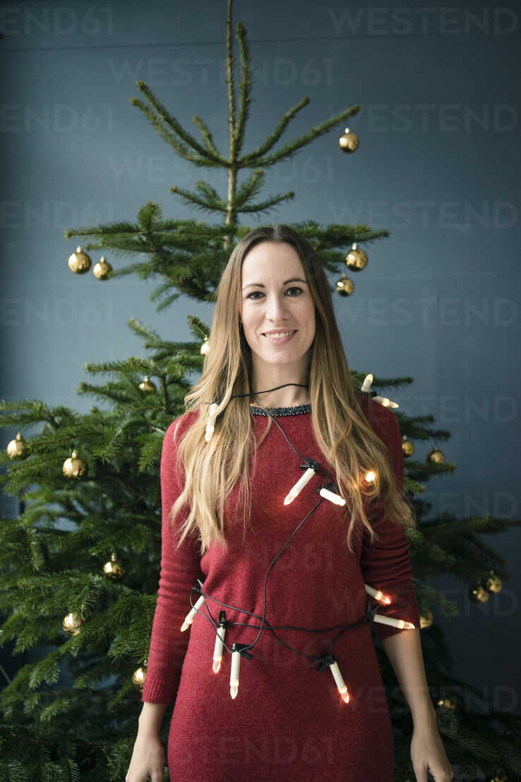 Portrait of smiling woman with chain of lights standing in front of Christmas tree - MOEF01352 - Robijn Page/Westend61