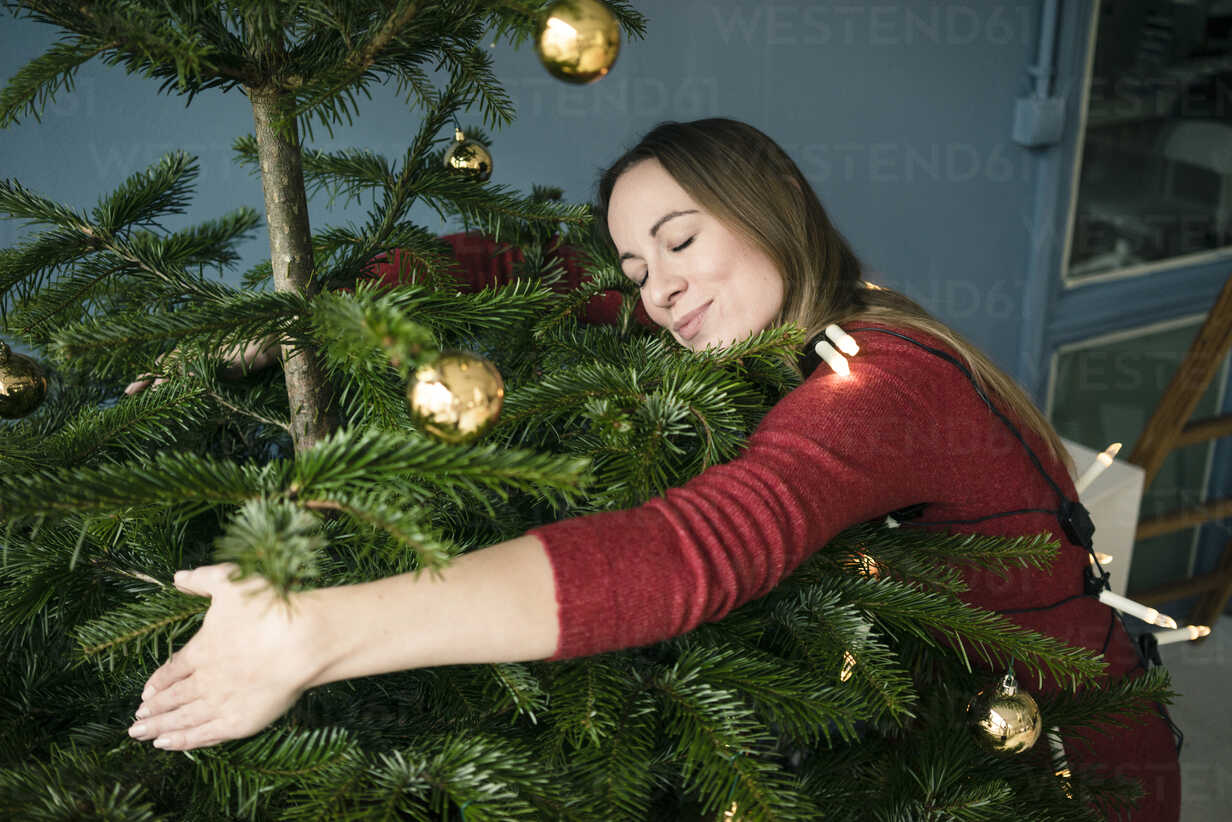 Woman hugging Christmas tree - MOEF01355 - Robijn Page/Westend61