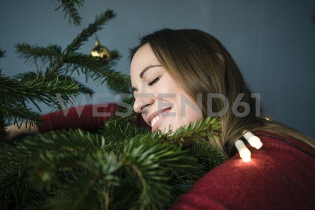 Happy woman hugging Christmas tree - MOEF01358 - Robijn Page/Westend61