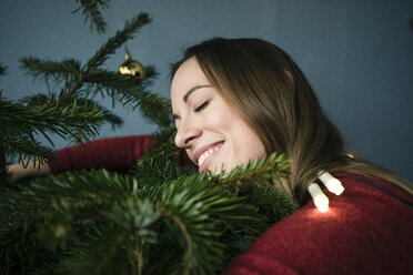 Happy woman hugging Christmas tree - MOEF01358