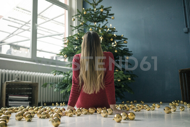 Back view of woman sitting on the floor with many golden Christmas baubles looking at Christmas tree - MOEF01361 - Robijn Page/Westend61