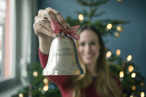 Woman's hand holding silver Christmas bell - MOEF01364