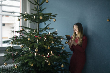 Smiling woman standing besides decorated Christmas tree using tablet - MOEF01370