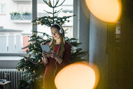 Smiling woman using tablet and headphones at Christmas time - MOEF01373