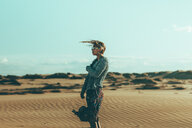 Young woman with windswept hair standing in desert landscape - OCAF00258