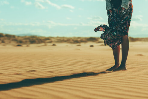 Legs of young woman standing in sand dune - OCAF00261