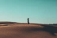Young woman with windswept hair standing in desert landscape - OCAF00264
