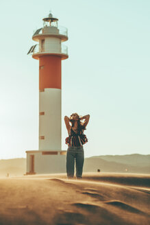 Young woman with windswept hair standing in desert landscape at lighthouse - OCAF00270