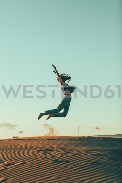Young woman jumping in desert landscape - OCAF00276 - Oriol Castelló Arroyo/Westend61