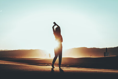 Silhouette of woman standing in desert landscape at sunset - OCAF00279