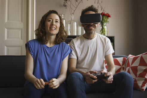 Smiling woman sitting by man playing on virtual reality headset in living room at home - FSIF03121