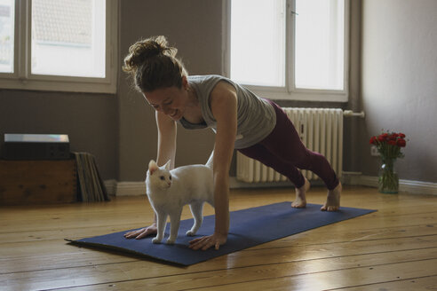 Smiling woman practicing plank position over white cat on exercise mat at home - FSIF03127