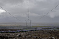 Row of electricity pylons on field against cloudy sky, Highlands, Iceland - FSIF03142