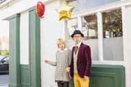 Young couple holding balloons and looking away while standing against window - FSIF03151